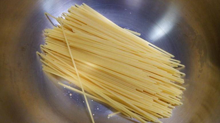 ホットクック内鍋に、半分に割ったスパゲッティ投入